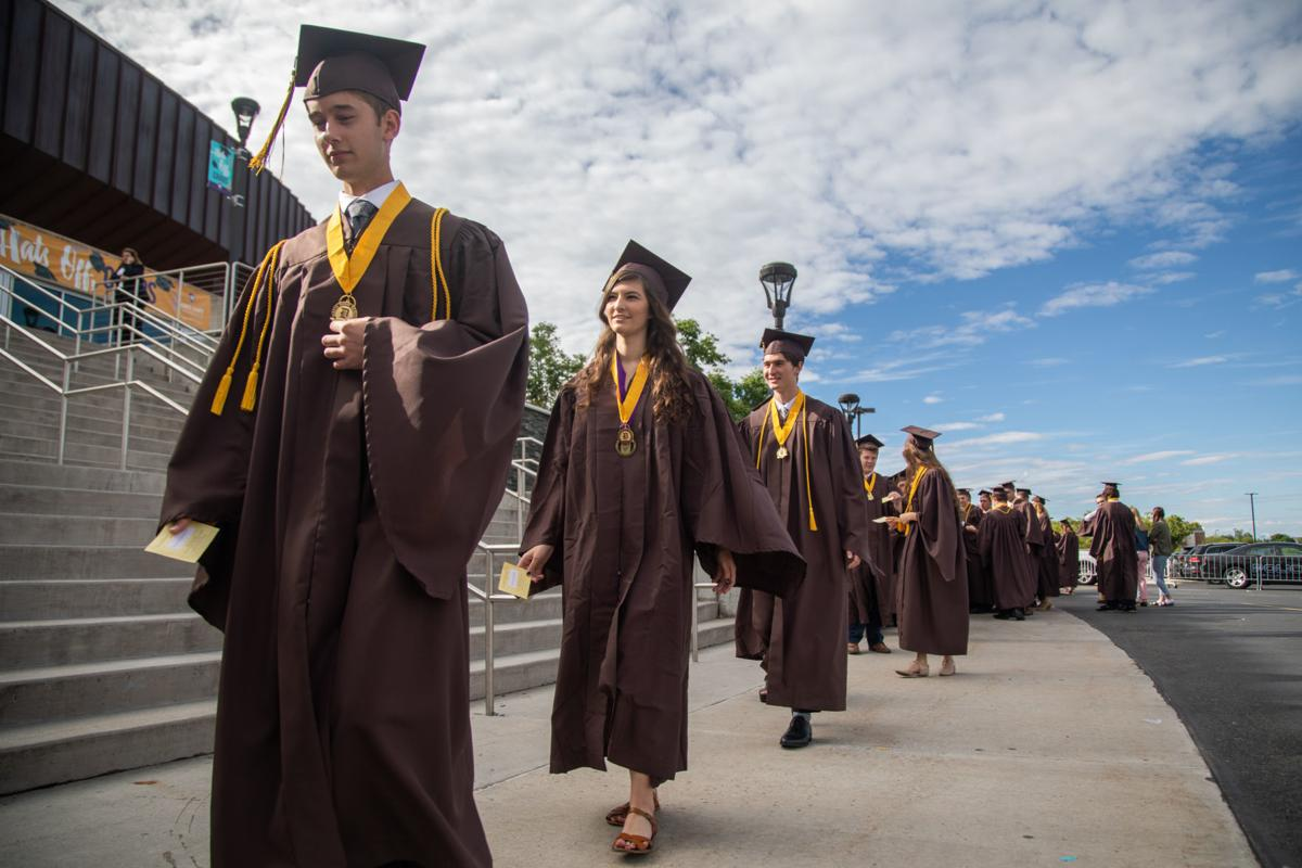 high school graduates wearing caps and gowns